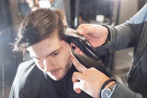 Master cuts hair and beard of men in the barbershop, hairdresser makes hairstyle for a young man. Barber work with clipper machine in barbershop.