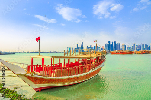 Perspective view of a traditional wooden dhow in foreground with seafront of Doha Bay and skyscrapers of West Bay skyline on background Canvas Print