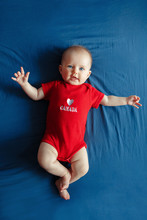 White Caucasian Smiling Baby Boy Girl With Blue Eyes Lying On Bed At Home On Canada Day. Newborn Infant Child In Red Onesie Romper Celebrating National Holiday July 1. View From Top Above