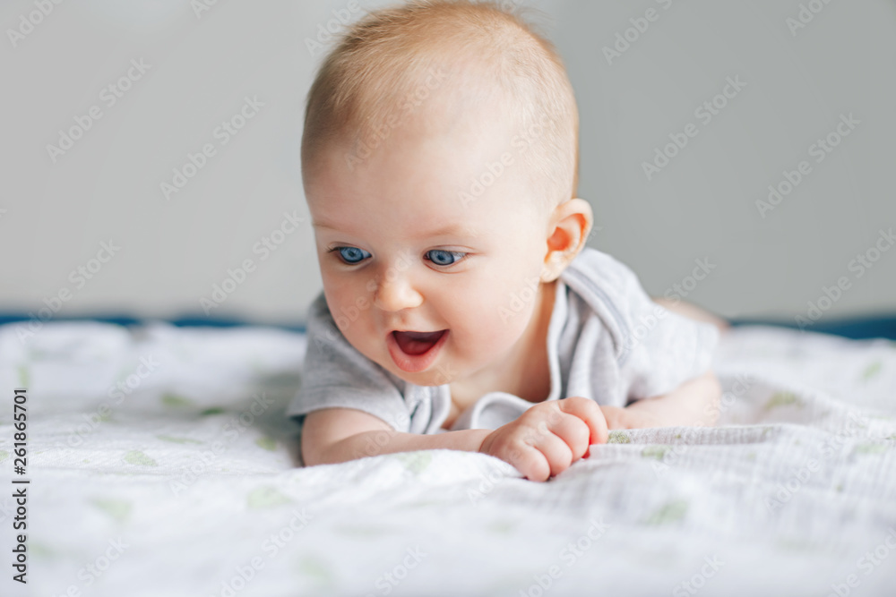 Fototapety, obrazy: Closeup portrait of adorable funny white Caucasian baby with blue eyes lying on tummy belly on bed. Aware cute newborn at home. Curious child boy girl with natural emotion.