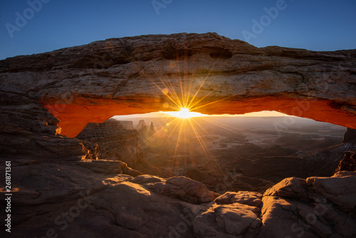 Printed kitchen splashbacks Brown Mesa arch in Canyonlands National Park just outside Moab Utah. The sun beams like a sunstar through the window of the desert arch. The cold snow contrasts the orange glow.