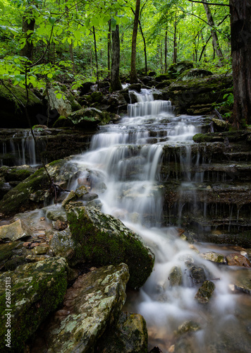 Arkansas cascade deep in the lush Ozark mountains. Lush green Spring foliage, soft water and the rocky ridge gives a textured contrast to the forest scene deep in the dense wilderness.  Wall mural