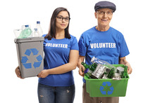 Young Female Volunteer And A Senior Man Volunteer With Recycling Bins
