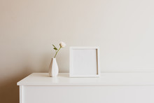 Close Up Of Single Rose In Small White Vase Next To Blank Square Picture Frame On Sideboard Against Neutral Wall - Warm Matte Filter Effect