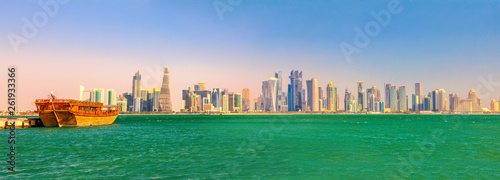 Fényképezés  Banner panorama of traditional wooden dhow in Doha Bay and skyscrapers towers of West Bay skyline