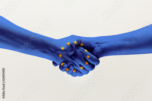 Fototapeta Cooperation agreement. Male hands shaking colored in blue EU flag isolated on gray studio background. Concept of help, commonwealth, unity of European countries, political and economical relations. obraz
