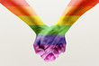 Right to choose your own way. loseup shot of a gay couple holding hands, patterned as the rainbow flag isolated on white studio background. Concept of LGBT, activism, community and freedom.