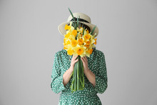 Woman With Bouquet Of Beautiful Daffodils On Light Background