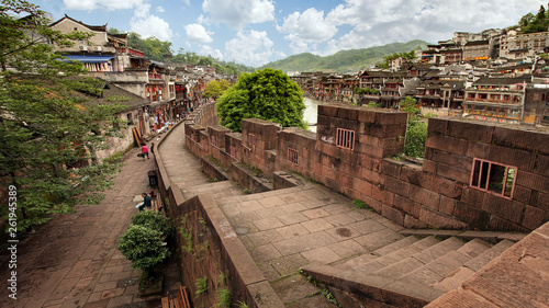 Garden Poster Old building Fenghuang Hunan/China - June 20, 2017: Tourists walk along the river embankment in old town Phoenix ancient town or Fenghuang County is a county of Hunan Province, China