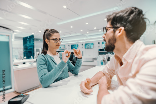 Young Caucasian charming brunette with ponytail and eyeglasses dressed casual explaining to seller which smart phone she want to buy Fototapet