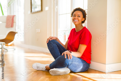 Poster Ecole de Yoga Beautiful young african american woman smiling confident to the camera showing teeth sitting on the floor at home