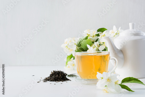 Fototapeta Cup of green jasmin tea white jasmine flowers, teapot