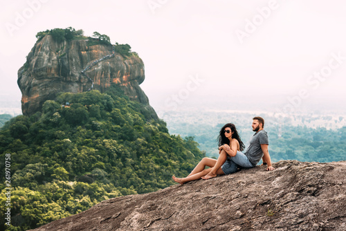 Zakochana para na skale podziwia piękne widoki. Chłopiec i dziewczynka na skale. Podróżuje zakochana para. Para na Sri Lance. Miesiąc miodowy w Azji. Mężczyzna i kobieta w Sigiriya. Para w górach