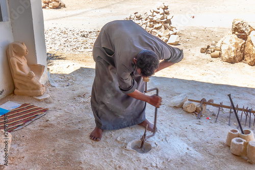 Photo Egyptian artisan drilling a cylindrical hole into granite stone for making a ves