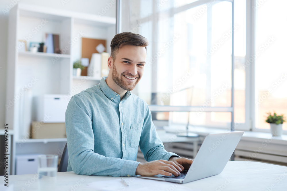Fototapeta Portrait of handsome young man working in office and smiling happily at camera, copy space