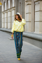 Brunette Girl Dressed In Yellow In White Peas Blues, Striped Pants And Hat Walks In The City Street On A Sunny Day