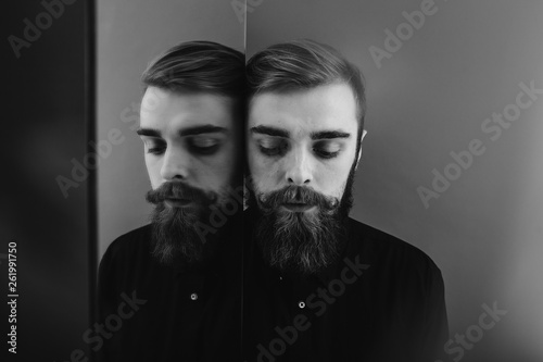 Fotografiet  Black and white photo of a man with a beard and stylish hairdo dressed in the bl