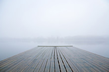 Wooden Footbridge On Lake. Mist Over Water. Foggy Air. Early Chilly Morning In Late Autumn. Peaceful Atmosphere In Nature. Empty Place For Text, Quote Or Sayings.
