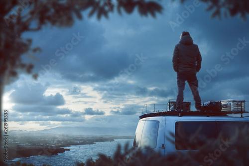 фотографія  Junger Mann steht auf dem Dach eines Camper Van