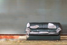 An Old Dark Gray  Sofa On Concrete Floor With Old Shutter Door