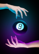 Hands With Magic Billiard Ball Number Eight On A Dark Background. Cyan And Purple Light