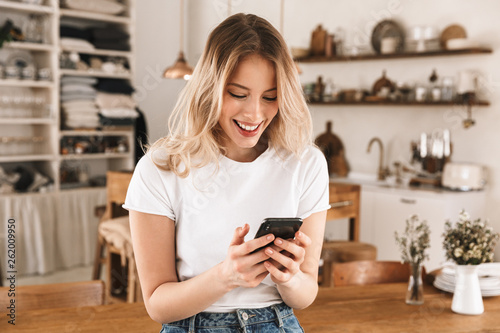 Portrait of cheery blond woman using smartphone while standing in stylish wooden Canvas Print