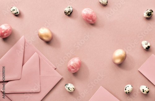 Easter flat lay on cream paper with quail eggs, greeting cards and envelopes