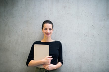 Young Business Woman With Clipboard Standing Against Concrete Wall In Office.