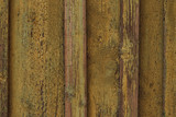 Old yellow peeling paint of wood surface. Old wooden fence. Сracked yellow paint on wooden boards. Vintage wood texture background