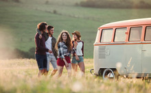 A Group Of Young Friends On A Roadtrip Through Countryside, Walking.