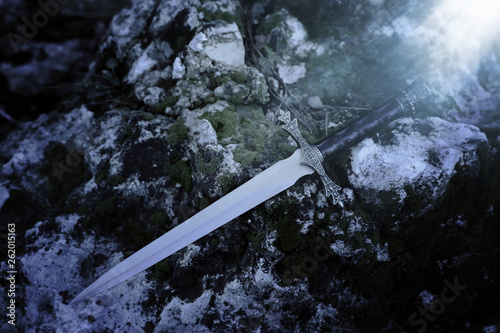 Fotografie, Tablou  mysterious and magical photo of silver sword over the stone covered with moss in the England woods