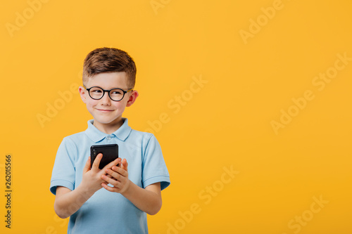 Fotografiet  handsome little boy is happy with the phone in hand, in glasses, dressed in blue