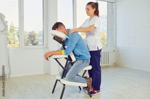 Valokuva  Woman massaging man in special stand