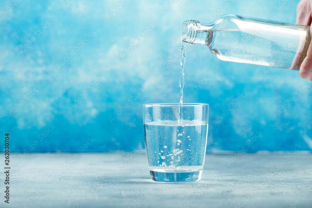 Fototapeta Pouring water from bottle into glass