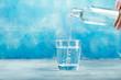 Leinwandbild Motiv Pouring water from bottle into glass