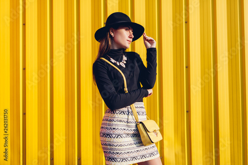 48582b1f Young stylish woman wearing beautiful outfit with handbag and hat. Spring female  clothes and accessories