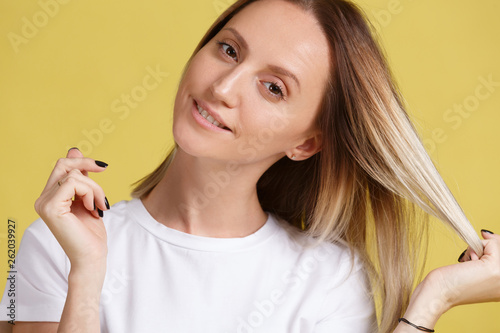 Fotografie, Obraz  Close-up portrait of a young charming blonde girl looking at the camera and touching the tips of her hair beautiful