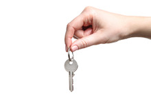 Female Hand Holding House Key On White Background