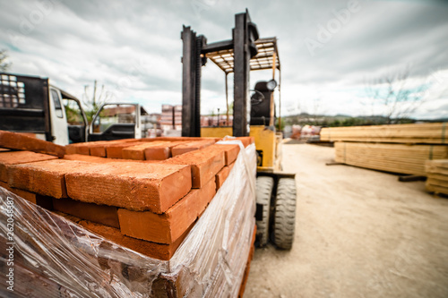 Obraz Fork lifter carry construction material clay bricks at the warehouse building site - fototapety do salonu