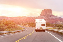 Road Trip By Motorhome Car With Background Of Mountains And Bright Orange Light Flare