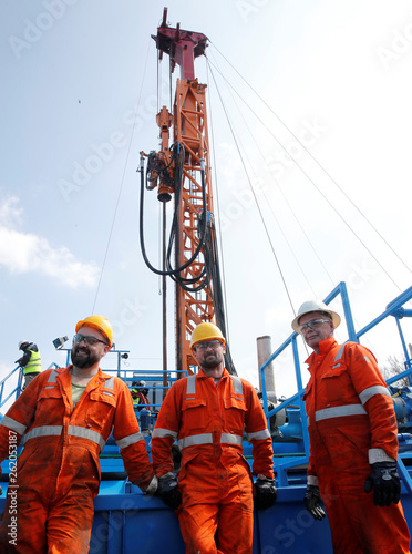 Workers stand in front of the drilling site of an
