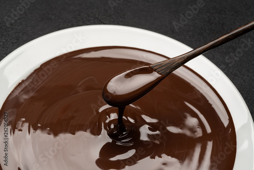 Fotografia, Obraz  Macro of Melted milk or dark chocolate swirl in plate and spoon on concrete back