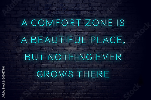 Fotografia  Night view of neon sign with motivational inscription about comfort zone