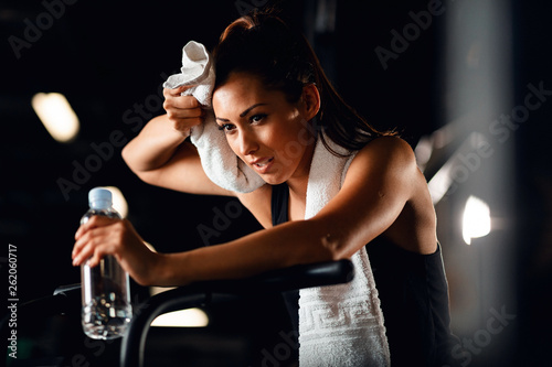Pinturas sobre lienzo  Tired sportswoman wiping sweat with a towel while exercising in a gym