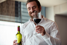 Smiling Mid Adult Man Holding Wine Bottle And Glass In Bar