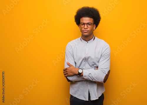 Fotografía  Young african american man over an orange wall crossing arms relaxed