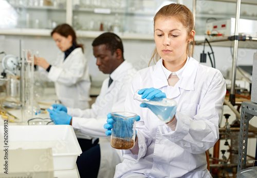 Serious woman lab scientist in glasses working with reagents and test tubes