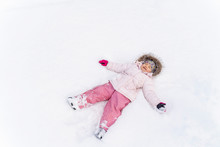 Cute Little Girl Lying In Snow...
