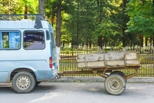 A Car With A Small Wooden Trailer On Wheels. The Vehicle Is Gray. Machine With A Homemade Trailer. Rest In Georgia.