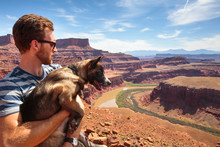 A Man Holds A Puppy While Looking Out Over A Bend In The Colorado River From A Viewpoint At The End Of The Short 0.3 Mile Gooseneck Trail In Canyonlands National Park, Utah. The La Sal Mountains Are In The Distance.